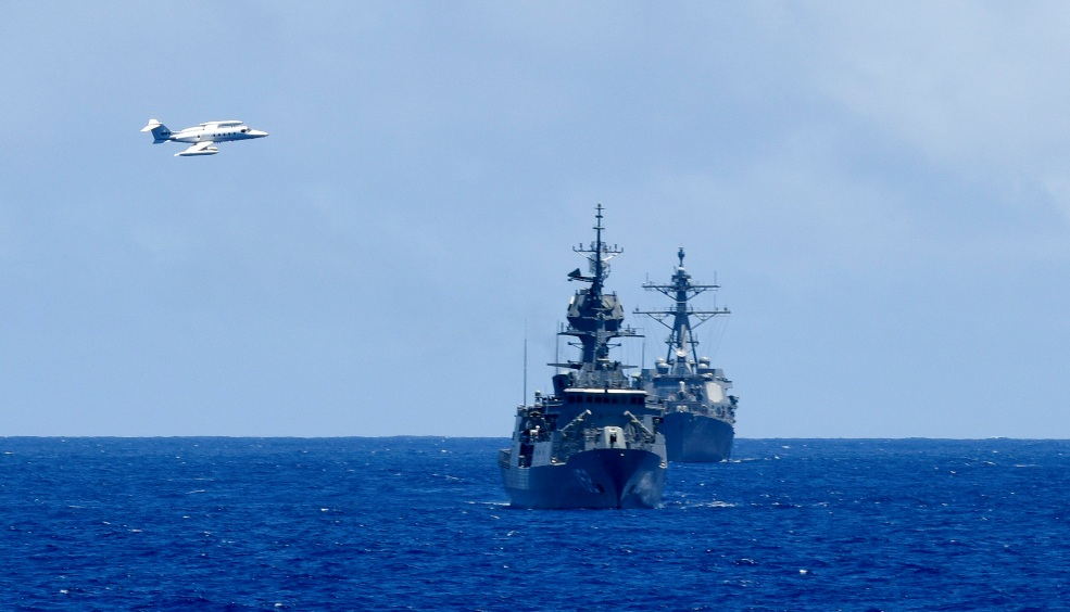Two small jet aircraft act as a simulated target while flying between the Royal Australian Navy HMAS Warramunga (FFH 152), front, and US Navy USS Howard (DDG 83) during Rim of the Pacific 2016. US Navy photo