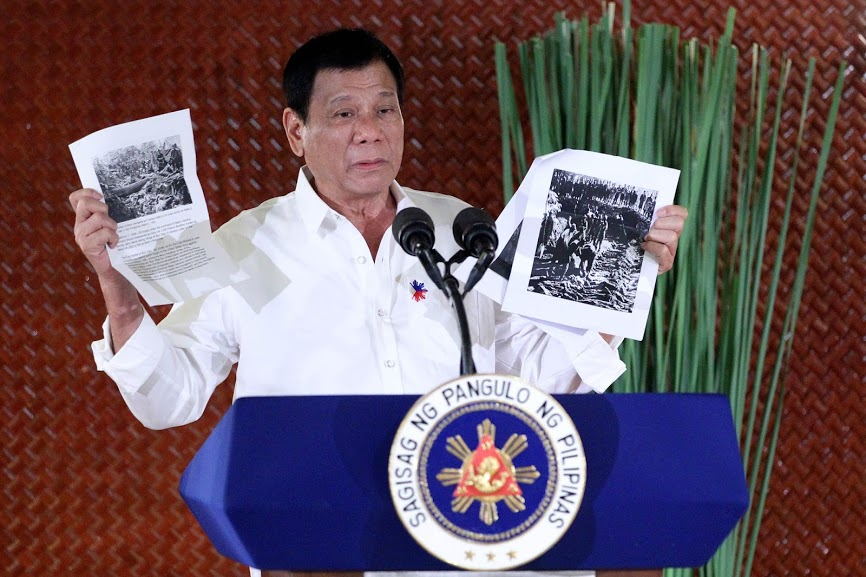 President Rodrigo Duterte shows to his new appointees pictures of the Bud Dajo Massacre during their oath taking at the Heroes Hall in Malacañan on September 12. Government photo